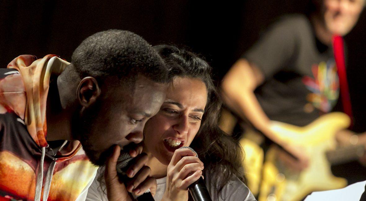 zwei Menschen singen und rappen leidenschaftlich mit Mikrofonen
