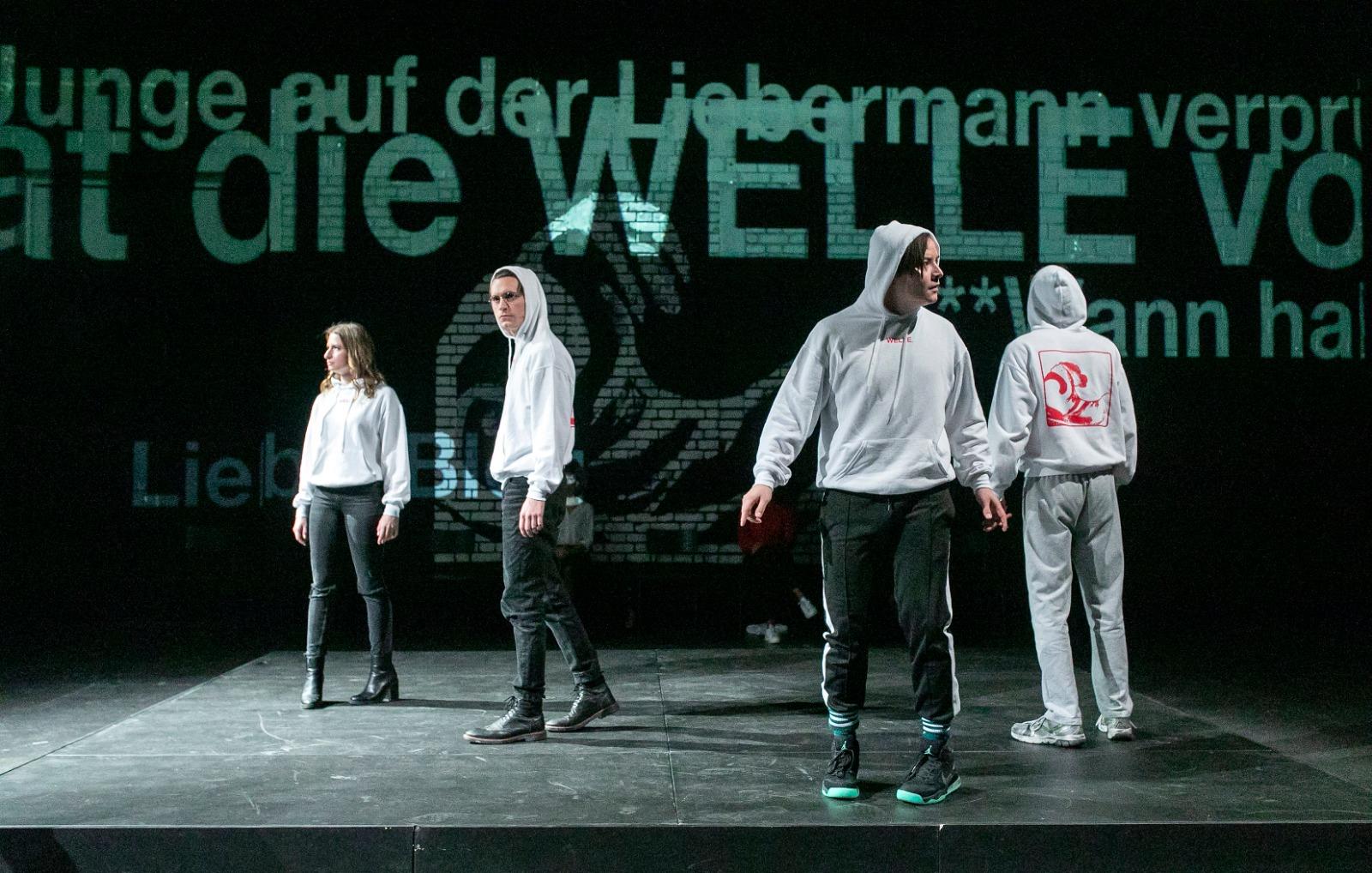 Szene aus dem Stück. Vier Schauspieler*innen stehen mit den selben Hoodies auf der Bühne